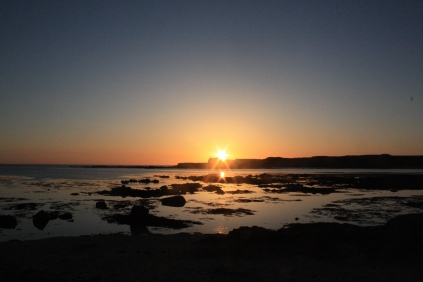 The sun begins to sink behind St Cwyfan